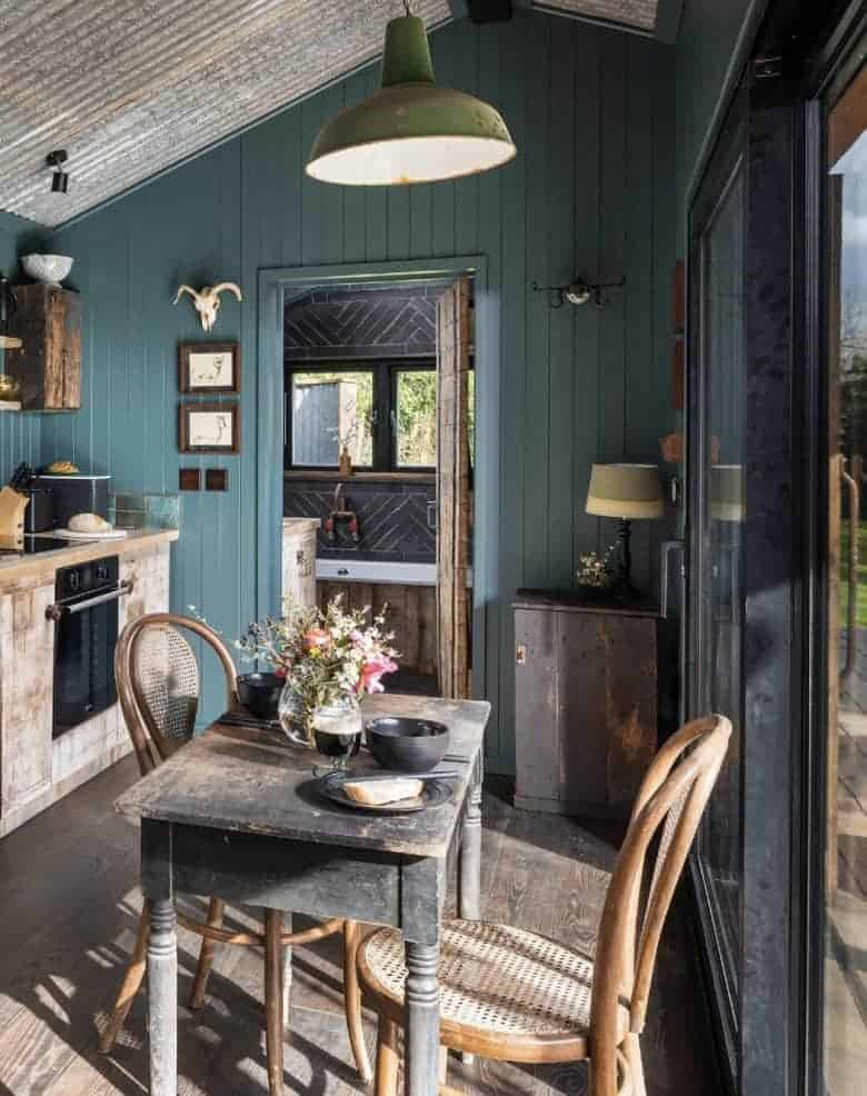modern rustic kitchen diner decorating idea - dark teal tongue and groove walls with reclaimed wood kitchen units, vintage dining table and industrial lighting from original btc with sliding doors bifold french opening on to dining terrace #modern #rustic #kitchen #diner #reclaimed #teal