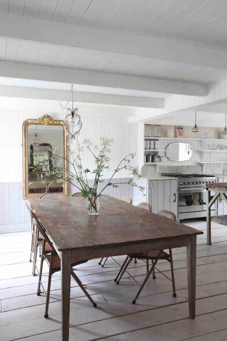 love this modern rustic coastal kitchen diner dining room with white washed painted tonque and groove panelled walls and lime washed floor boards with open shelving, rustic dark wooden dining table with vintage metal chairs and vintage mirrors vintage lighting and prints. Click through for more inspiring modern rustic decorating ideas you'll love #modernrustic #decorating #kitchen #dining #vintage #country #white #frombritainwithlove