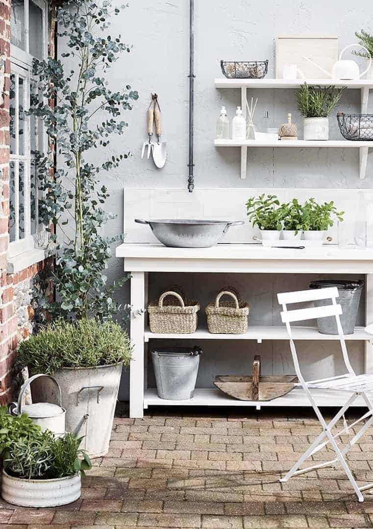 outdoor kitchen patio terrace, modern rustic white shelves with vintage galvanised watering can, tubs and plant pots with rustic baskets, wooden trugs and vintage wire work and garden tools. #modern #rustic #outdoor #kitchen