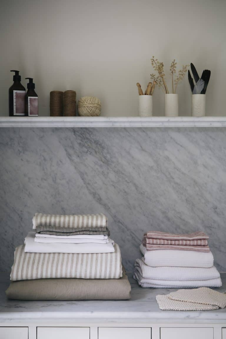 love this stack of linen in modern rustic utility laundry room with open shelves, marble splashback, painted vintage cupboard linen press and wooden airer