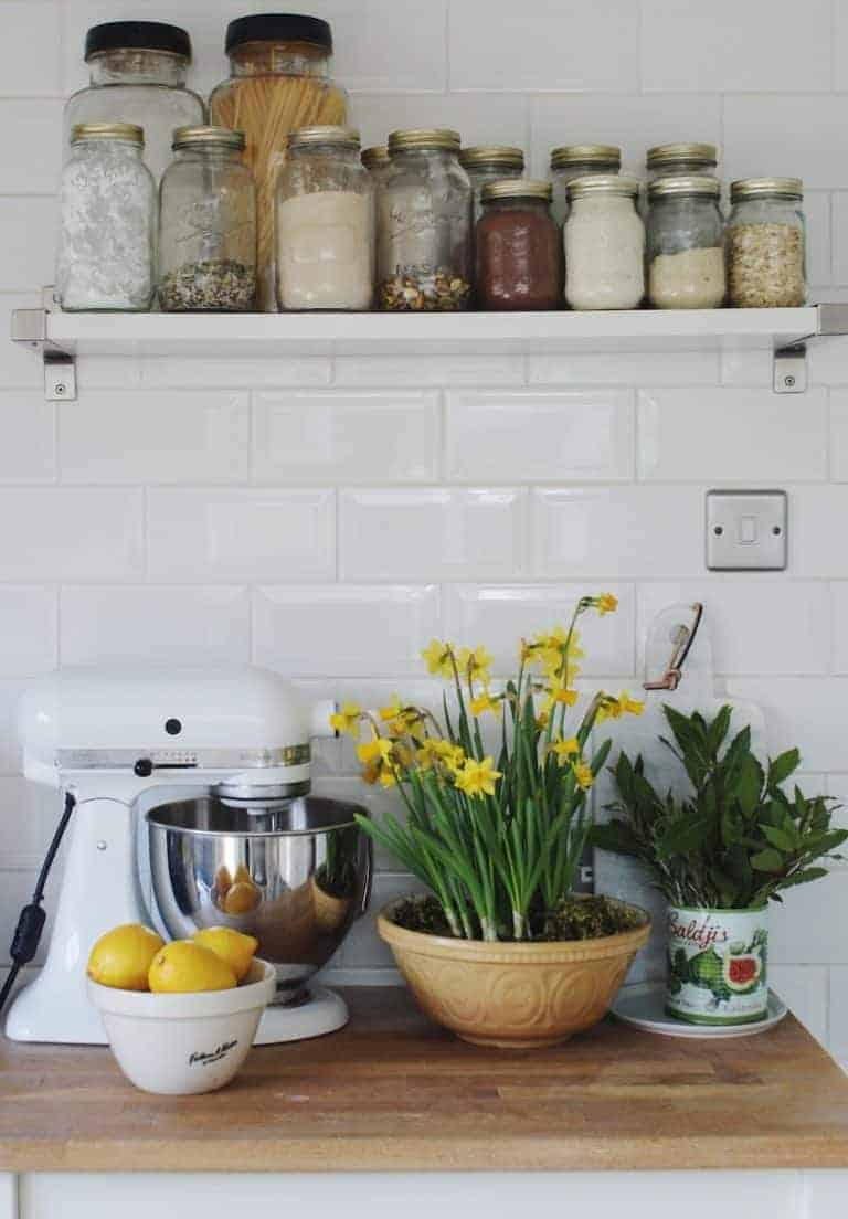 love this modern rustic kitchen with white mixer, spring flowers in vintage mixing bowl, old tins of herbs, open shelves with glass jars and white metro tiling