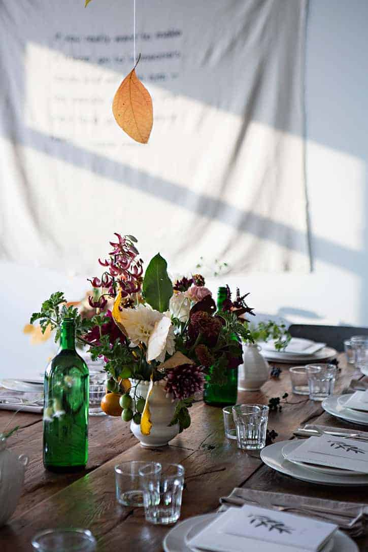 autumn flower arrangement idea with dahlias, geranium leaves, olives, citrus fruit and purple garden flowers below a falling autumn leaves table decoration by kinfolk sunday suppers. Just one of many beautiful fall autumn flower ideas you'll love to recreate in your own home #autumn #flowers #fall #arrangement #ideas #frombritainwithlove