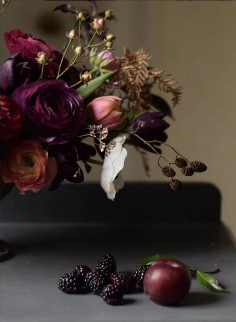 love this autumn flower arrangement by Sarah Diligent of Floribunda Rose using british flowers including jewel shade ranunculus, tulips, anemone, blackberries, seed heads, ferns, autumn leaves, foraged foliage and seasonal berries and greenery. Click through for more autumn flower arrangement ideas you'll love to make #frombritainwithlove #mybritainwithlove #britishflowers #autumnflowerideas #autumnleaves