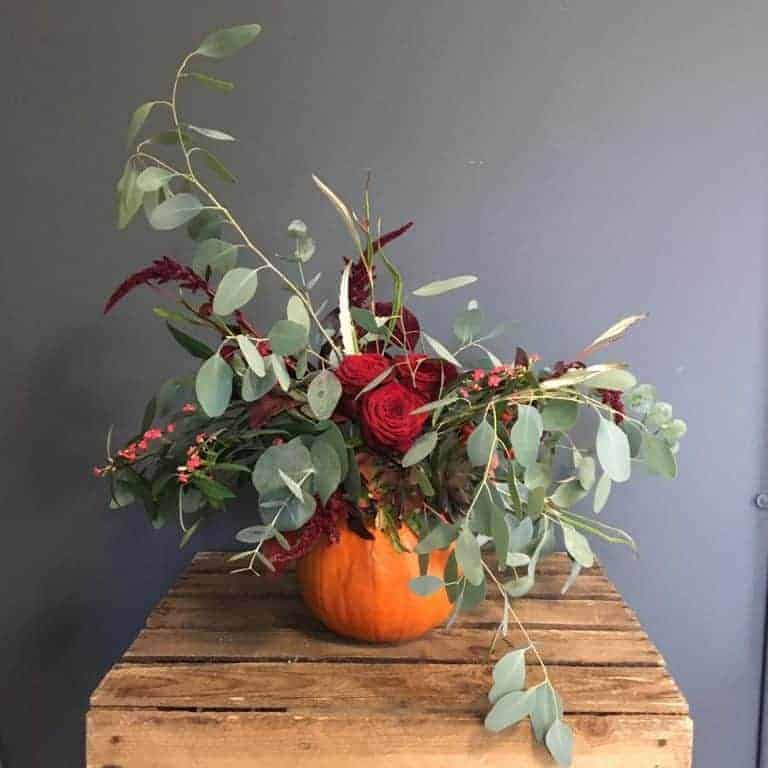 love this seasonal autumn flowers arrangement in a pumpkin with orange roses, eucalyptus and berries. click through for stunningly beautiful autumn flower arrangement ideas you'll love