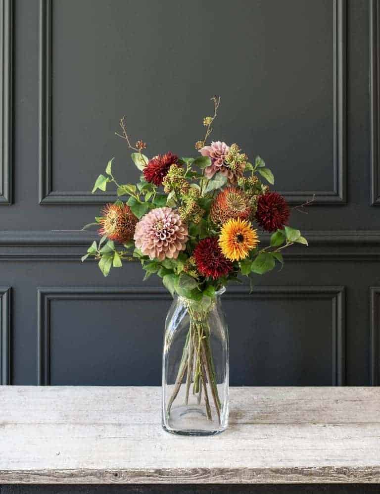 love these seasonal autumn faux flowers in orange and red in simple glass jar by Philippa Craddock. Includes faux chrysanthemums, zinnias, natural greenery and blush dahlias. Click through for details on where to buy them as well as other creative autumn flower arrangement ideas you'll love. #frombritainwithlove #mybritainwithlove #fauxflowers #autumnflowers #autumnflowerideas #fakeflowers