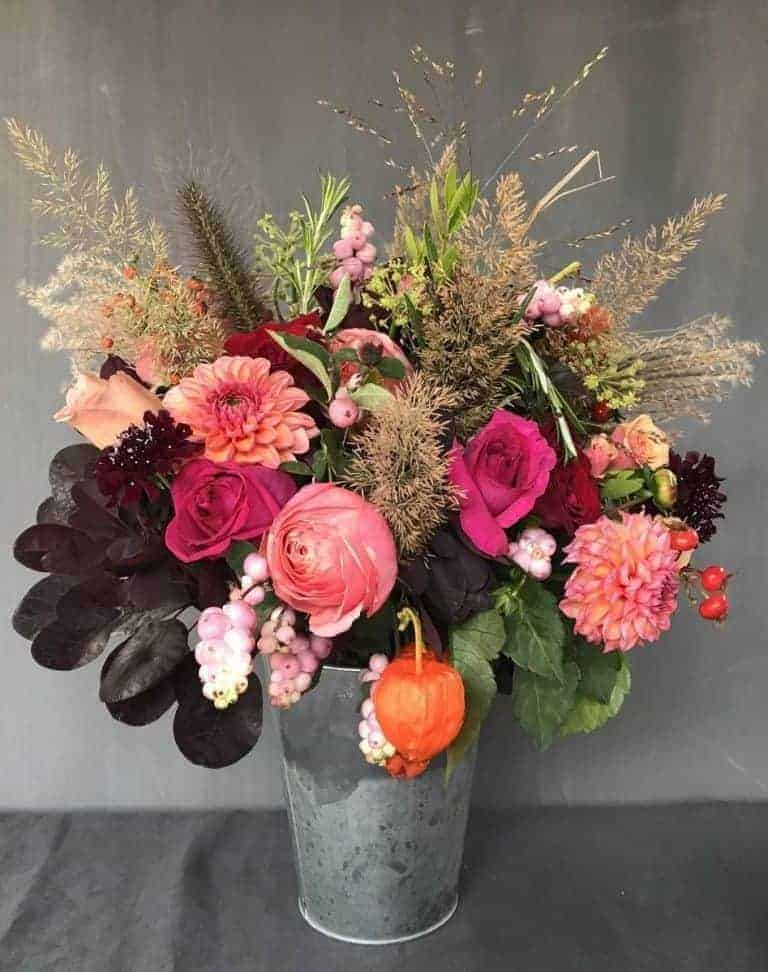 love this seasonal autumn flower arrangement of bright roses, chinese lanterns, grasses, chrysanthemums with foliage and seasonal berries. Click through for more utterly beautiful autumn flower arrangement ideas you'll love to make #frombritainwithlove #mybritainwithlove #britishflowers #autumnflowerideas #dahlias #scentedroses