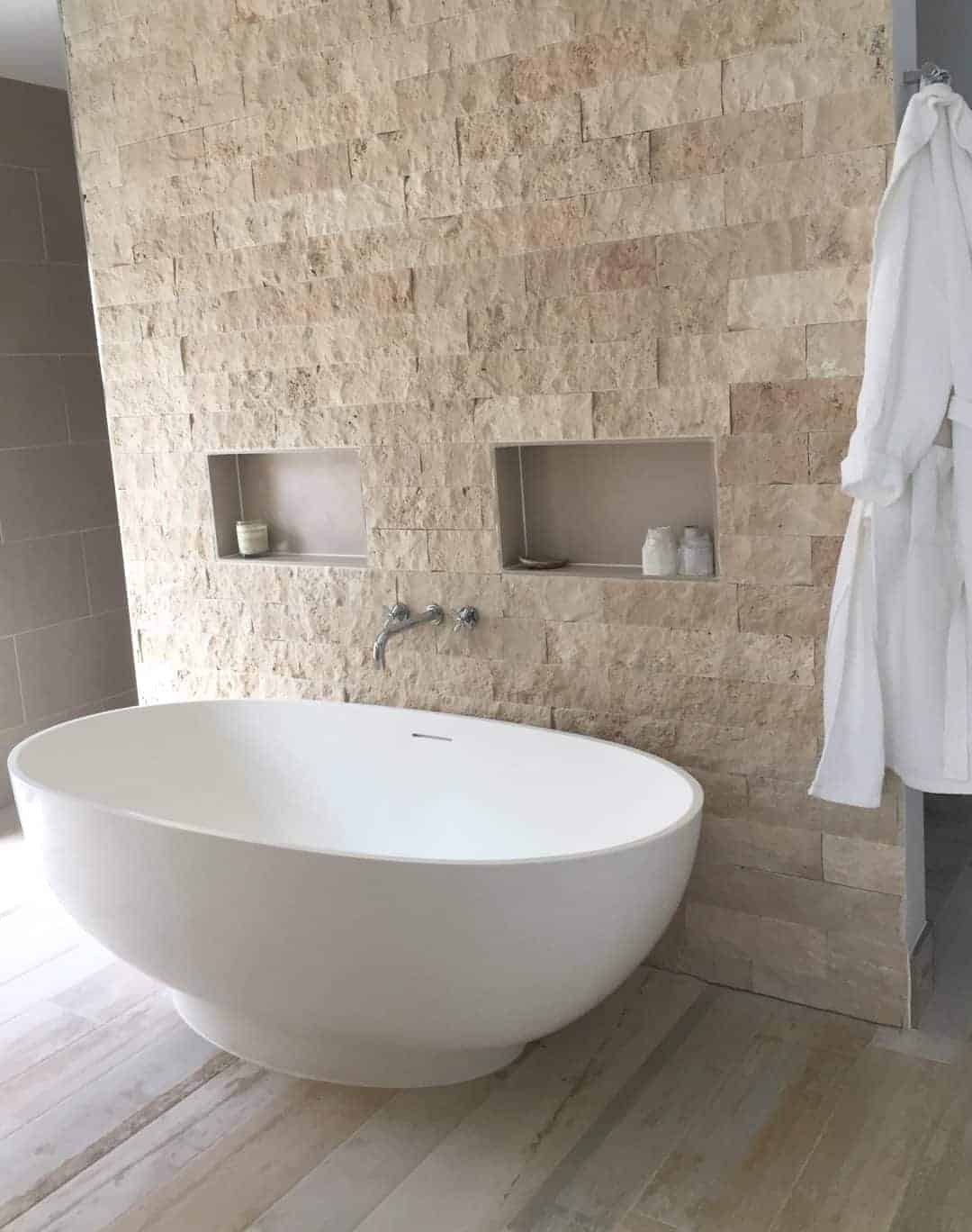 What about this idea to create the perfect minimal modern coastal bathroom? Driftwood effect floor tiles, white freestanding corian bath and textural stone wall. Click through for more inspiring images of this dream beach house in Cornwall