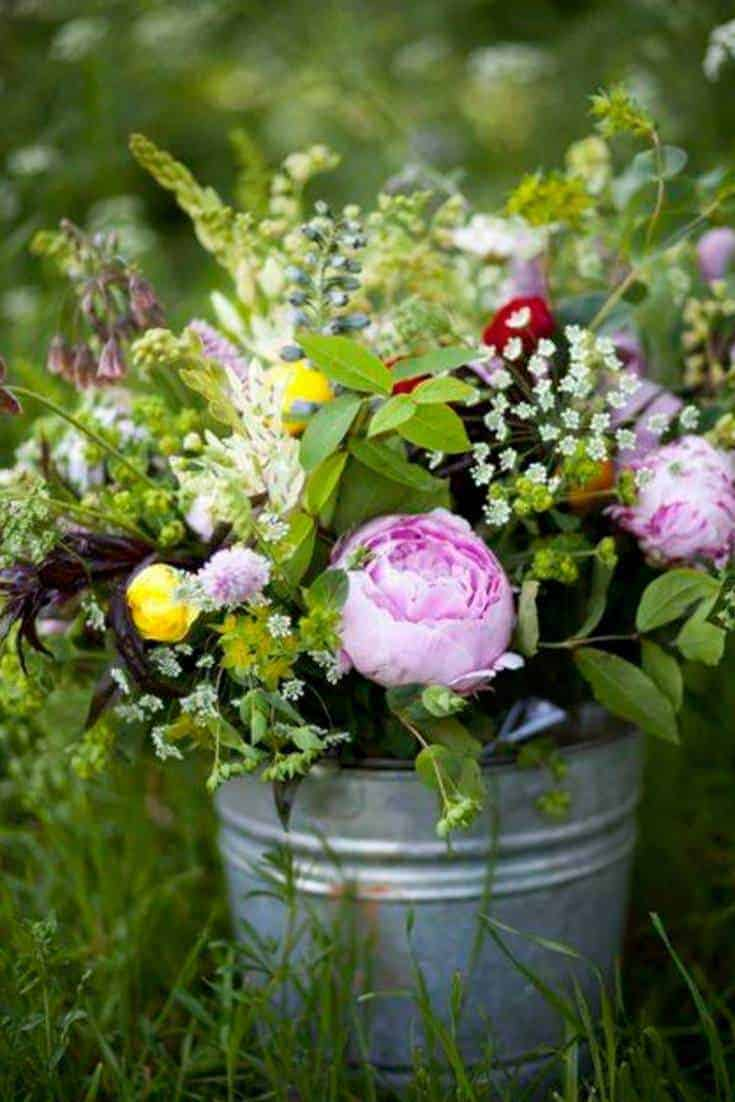 love how peonies, herbs and simple country blooms are arranged in vintage galvanised tin bucket. Perfect country wedding style. Click through for more inspiring ideas you'll love