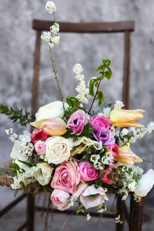 beautiful vintage country flowers with vintage chair. Perfect for a rustic wedding theme. Click through for inspiring country wedding flower ideas you'll love