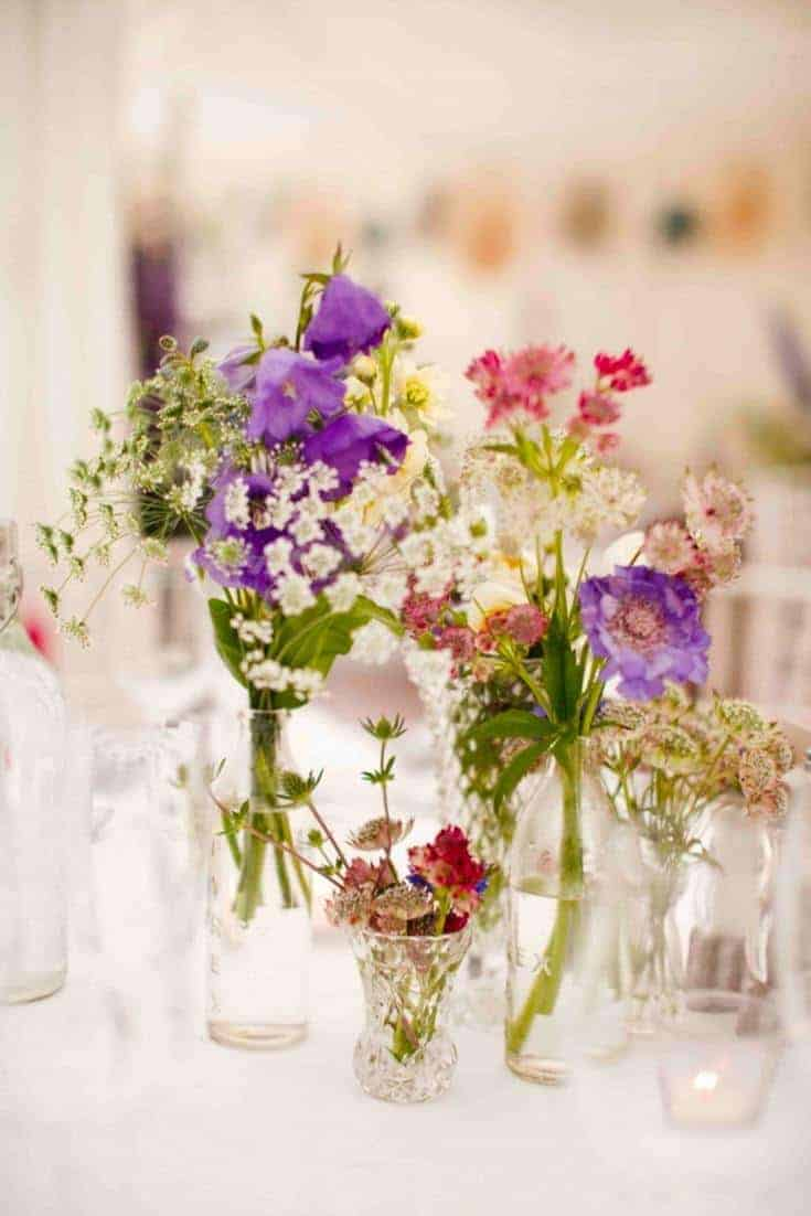 love simple blooms and wild flowers grouped in glass jars of different sizes for a pretty country wedding. Click through for inspiring ideas for creating a beautiful rustic wedding
