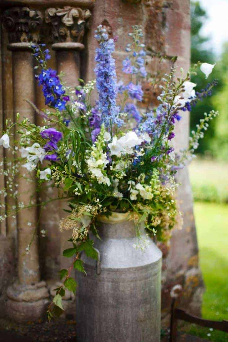 love this country style delphinium and cottage flowers in vintage churn wedding flowers. Click through for more beautiful country wedding flowers ideas to inspire you