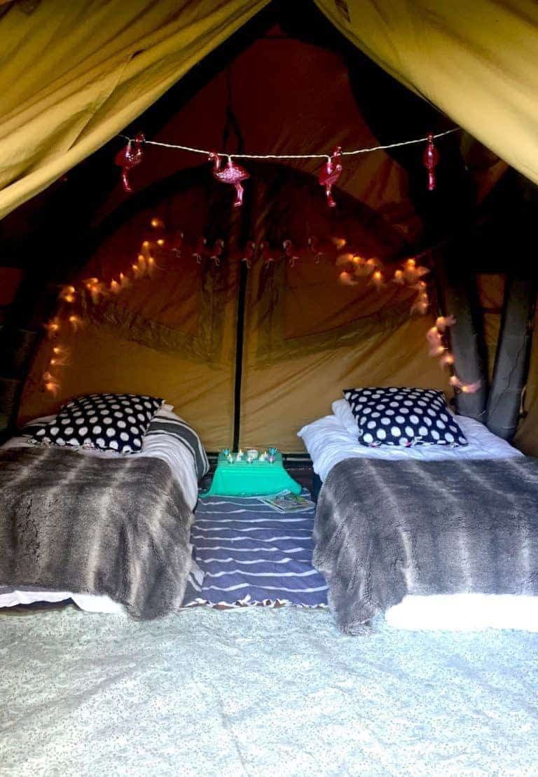 wilderness festival decorated tent meadow camping flamingo lights, fur throws and tea lights