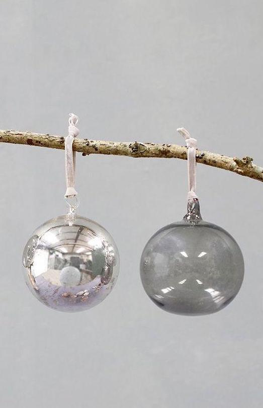 love these glass silvered and smoked glass baubles with blush pink velvet ribbon ties for a scandi christmas tree. click through for more special christmas decorations you'll love to hang year after year