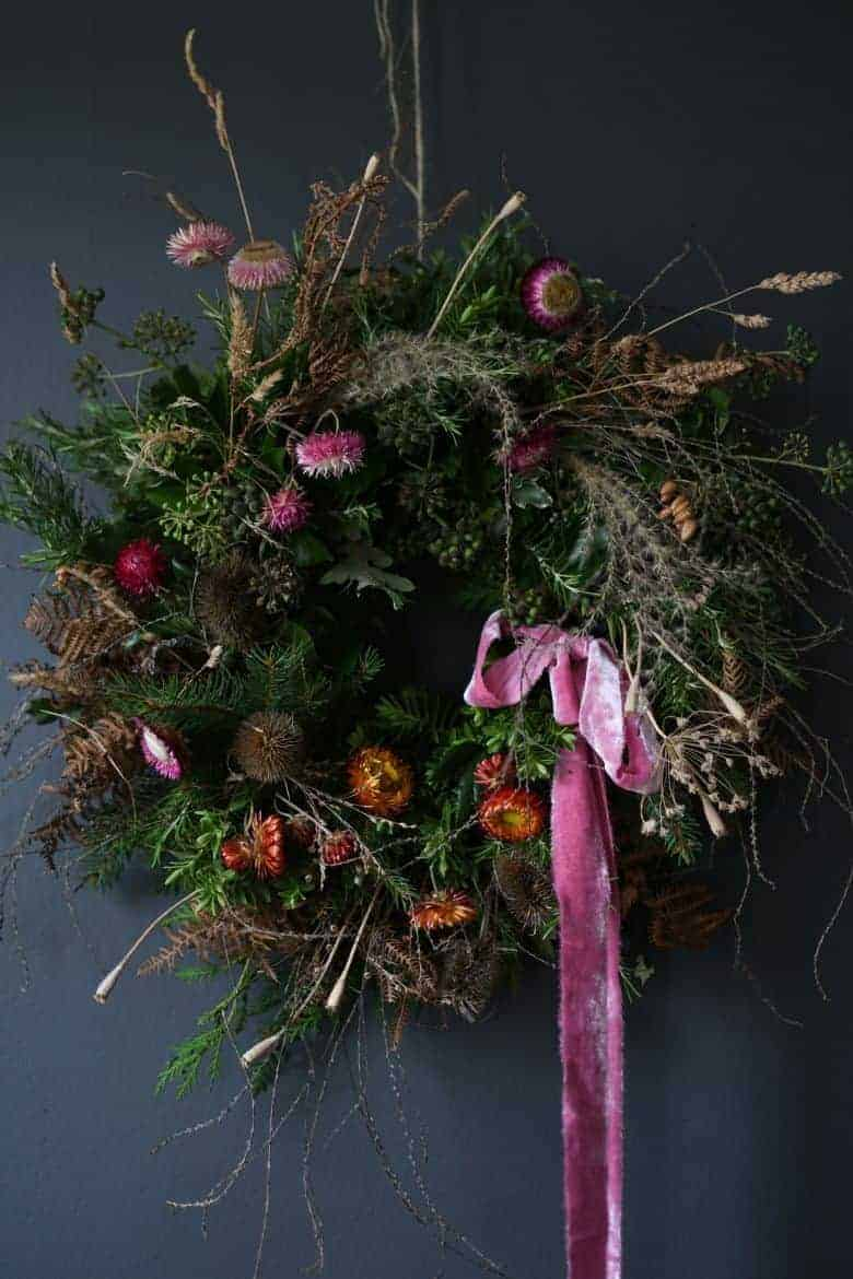love this contemporary christmas wreath by leigh chappell combining foraged foliage and greenery with dried stems and pretty strawflowers or helichrysum in pinks and reds - we've shared links to book up the online workshop to make one with Leigh as well as lots of other inspiring holiday wreath ideas #christmas #wreath #holiday #tutorial #workshop #diy