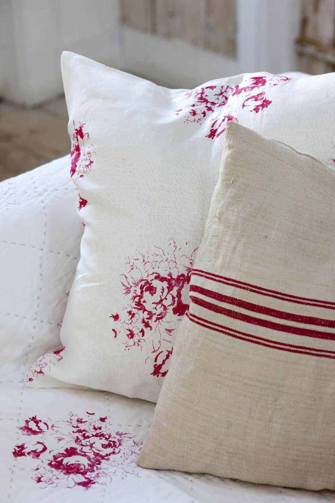 love this red and white Hatley cerise floral linen by cabbages and roses mixed with red stripe natural linen cushions. Click through for more details and to discover other beautiful faded floral linens you'll love