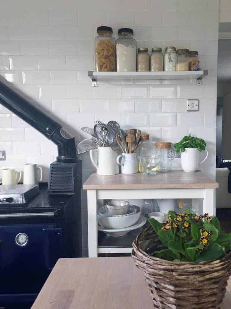 love this contemporary country kitchen look with white metro tiles, blue aga and open shelf with mason storage jars and white ceramaic jugs