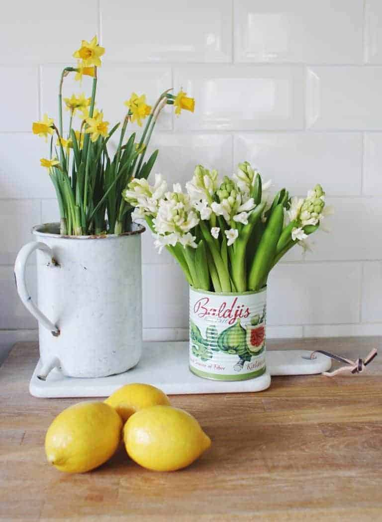 love these simple white hyacinths yellow narcissi in vintage enamel and tin