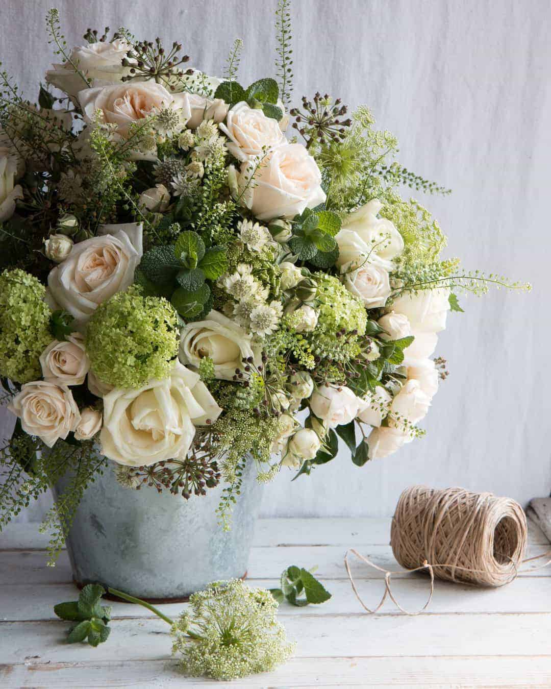 love these pale pink, white and lime green spring flowers by The Real Flower Company - margaret merrill scented roses, fresh mint, seed heads, lime white wild flowers, blossom in a galvanised metal pot. Click through for more beautiful spring flower arrangement ideas you'll love