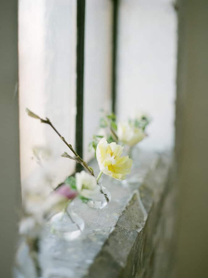 love this simple spring flower arrangement of yellow tulips, white anemone, magnolia and blossom in simple glass jars on stone windowsill. Click through for more creative ideas you'll love