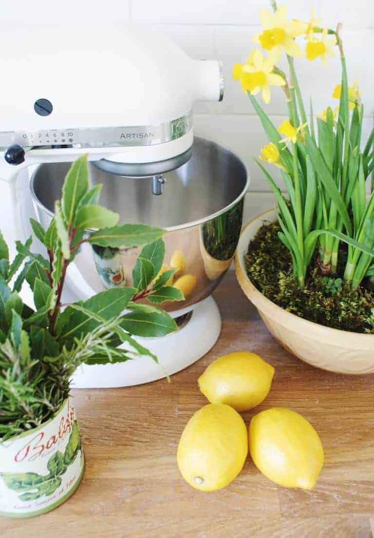 love this white mixer with spring narcissi daffodils in white kitchen with yellow