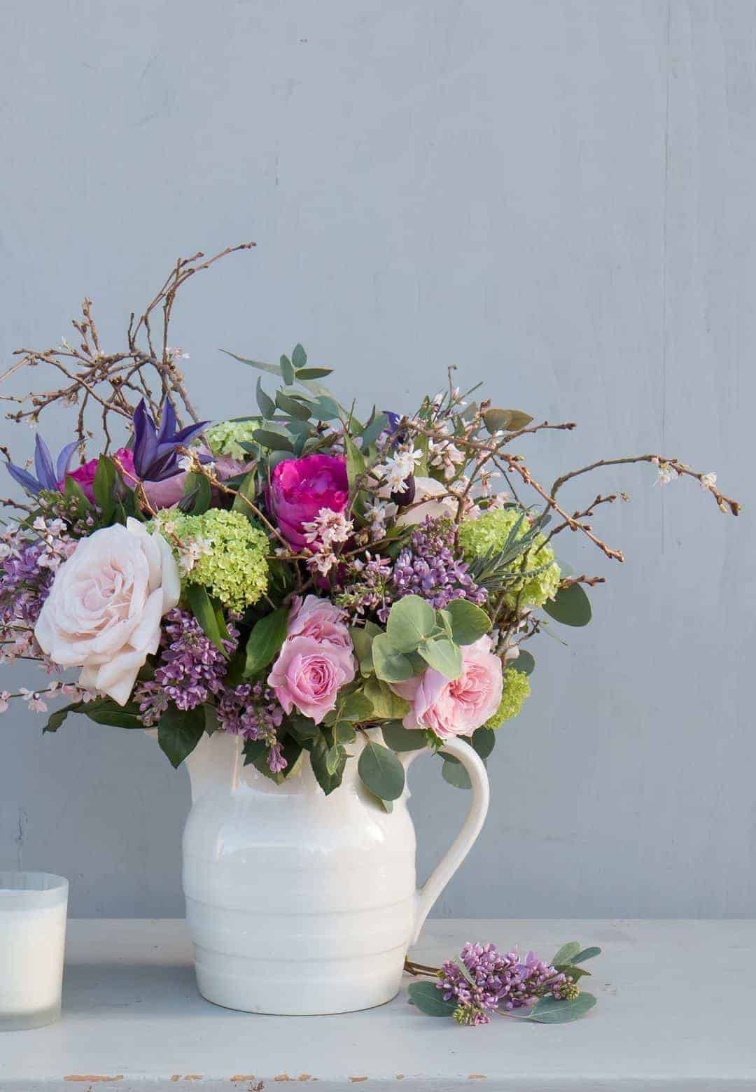 love these simple spring flowers in white creamware jug by The Real Flower Company - pale pink early roses, blossom, twigs, lilac and aromatic herbs. Click through for more beautiful spring flower arrangement ideas you'll love