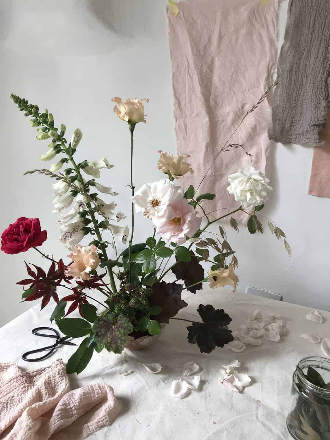 love these early summer spring flowers by worm - roses, foxgloves and foliage loosely arranged to create a contemporary arrangement. Click through for more spring flower arrangement ideas you'll love to try - simple DIY ideas