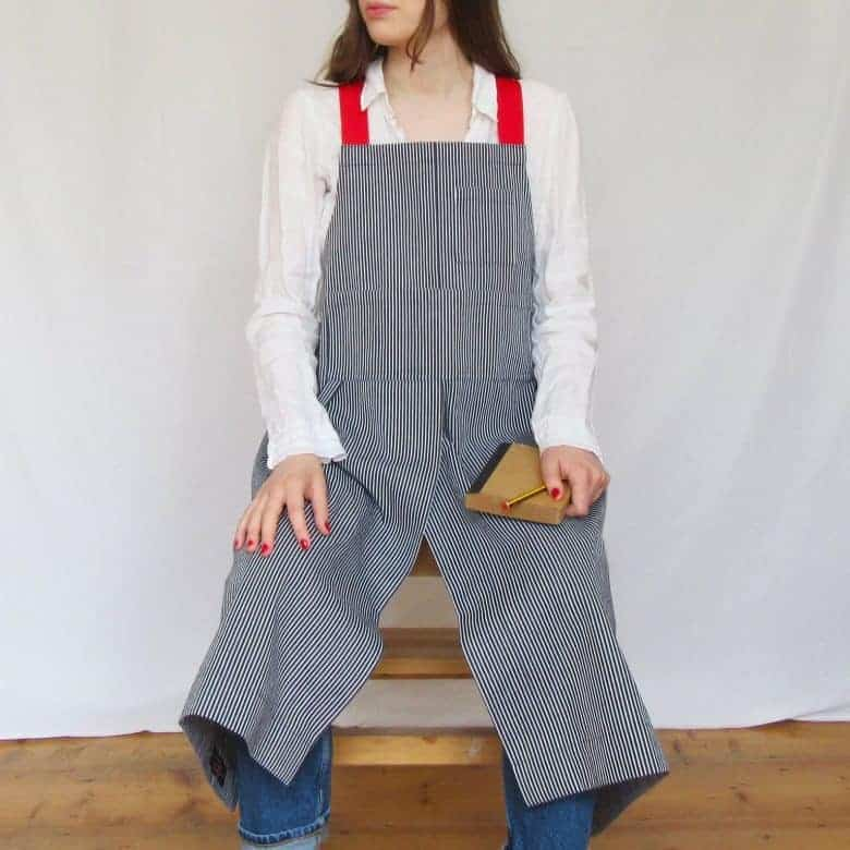 love this cross back apron handmade in ticking denim fabric with red straps. The high split is perfect for pottery makers allowing for easy access to the potter's wheel #artisan #apron #crossback #frombritainwithlove #potter