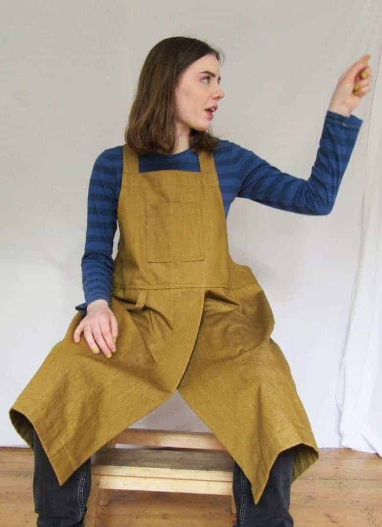 ochre denim cross-back apron for potters, artists, artisans and workwear. The high split is perfect for pottery makers allowing for easy access to the potter's wheel #artisan #apron #crossback #frombritainwithlove #potter