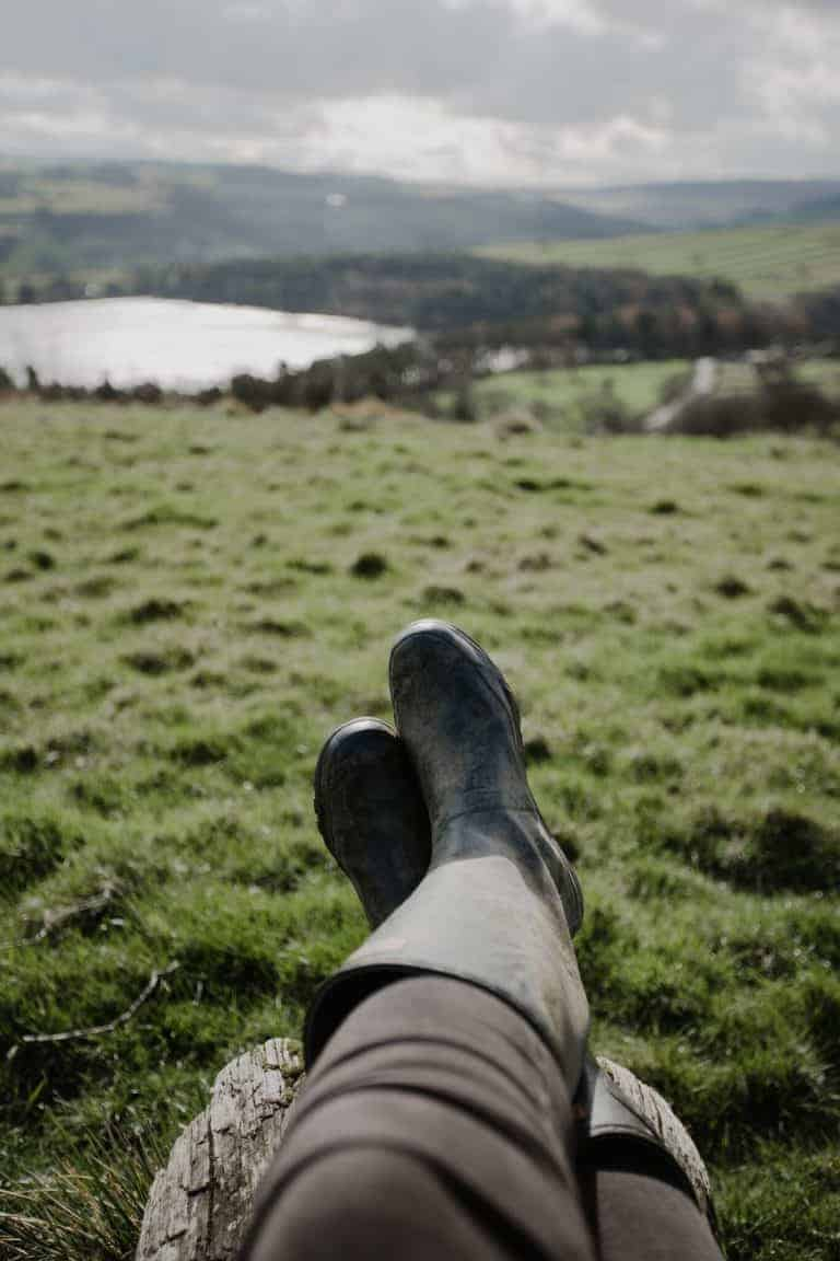 love this image of wellies and old log bench simple pleasure - taking in the view of the peak district hills and lake