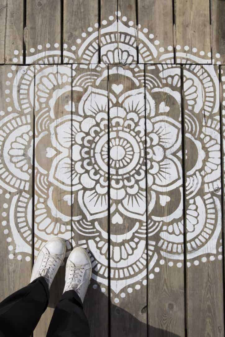 love this white painted mandala stencilled pattern on natural wood decking. Click through for more paint stencilling ideas you'll love