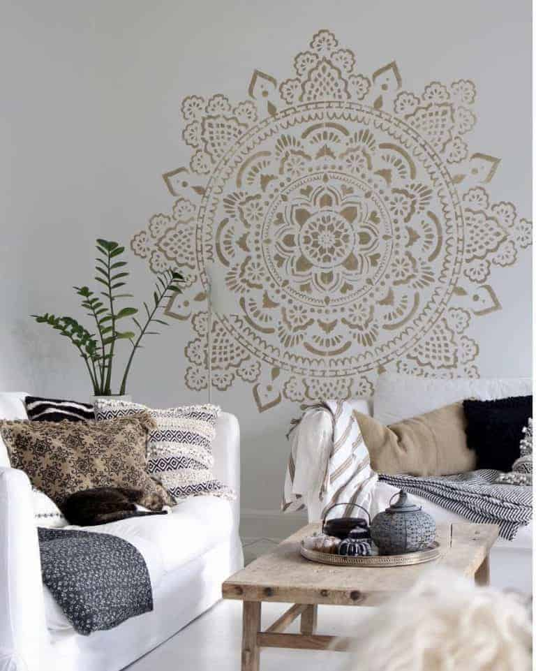 love this dark gold bronze mandala painted wall stencil with an ibiza vibe with white floorboards and white sofa. Click through for more stencil and paint stencilling ideas you'll love