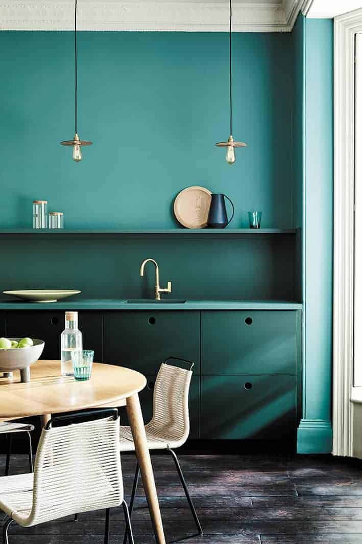 love this dark green paint colour - Harley Green wall below shelf and wall return and units; Tea with Florence teal green on upper wall. Love how the greens work together and contrast with the light wood table and industrial lighting pendants. Click through for more green paint colours you'll lvoe