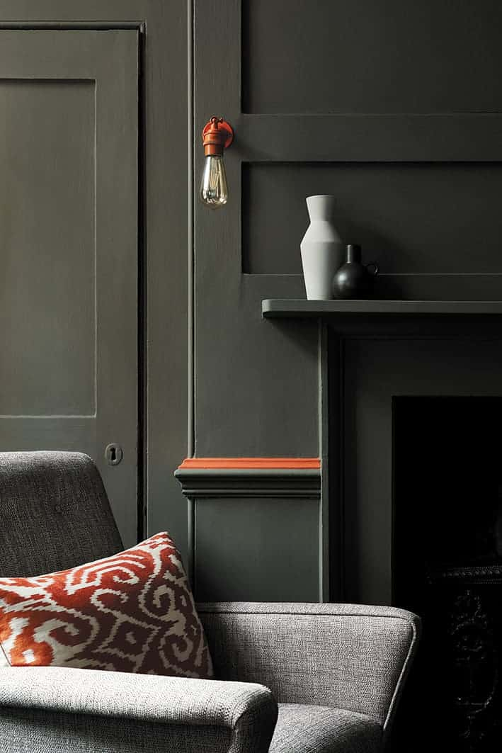 love these dark green walls and fireplace in living room with pop of orange by Little Greene. Click through for more green paint colours you'll love