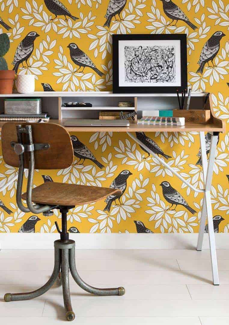 missprint songbird summer love this yellow wallpaper with birds made in England with black birds and white leaves. Click through for more beautiful wallpaper ideas you'll love to try in your home
