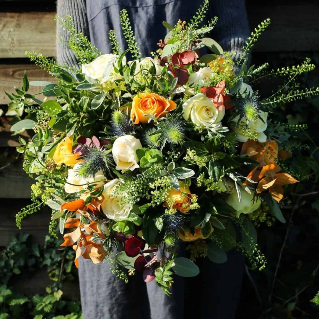love this autumn flower bouquet by The Real Flower Company including orange roses, autumn leaves, cream roses and herbs
