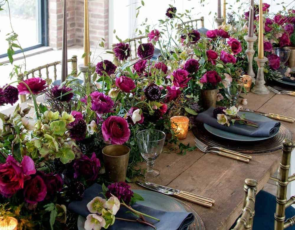 love this christmas flower arrangement using dark red and purple roses with lime white hellebores and rustic wooden table and brass with candles. Click through for more DIY christmas flower centrepiece ideas you'll love to try this holiday season