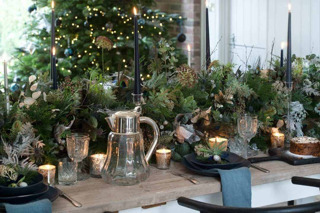 love this rustic christmas flower arrangement table centrepiece by philippa craddock with evergreen foliage, peacock feathers, seed heads, silver ferns, black candles and rustic wood. Click through for more DIY christmas flower centrepiece ideas you'll love to try this holiday season