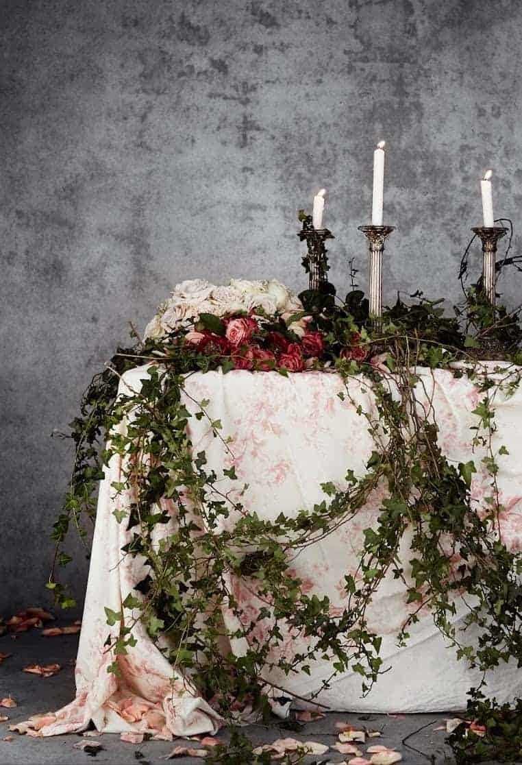 love this over the top almost gothic table decoration of roses and ivy with metal candlesticks and faded floral linens by Cabbages & Roses. Click through for more DIY christmas flower arrangement ideas you'll love to try this holiday season