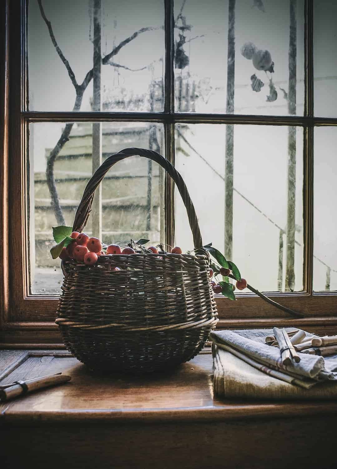 love this vintage basket with crab apples at old regency window with linen and wooden clothes pegs at The Regency Townhouse for the launch of Conscious Creativity by Philippa Stanton aka @5ftinf. Click through for a peek inside and a look behind the scenes at the launch workshop