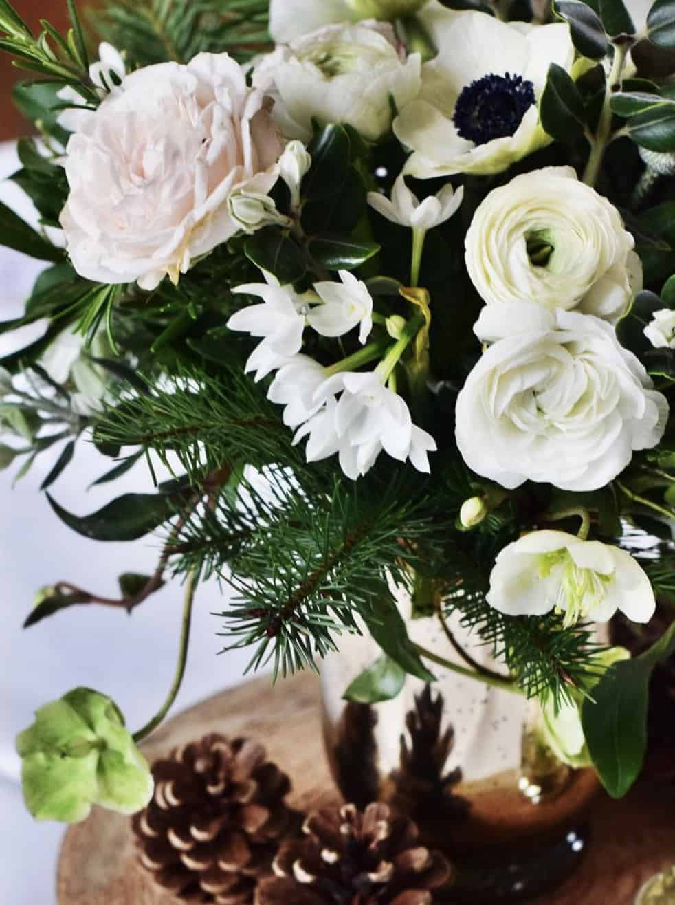 love this white and blush pink christmas flower arrangement idea by Floribunda Rose including white ranunculus, panda anemone, blush roses, paperwhite narcissi, lime hellebores and pine cones. Click through for more creative and beautiful DIY christmas table centrepiece ideas you'll love to try this holiday season