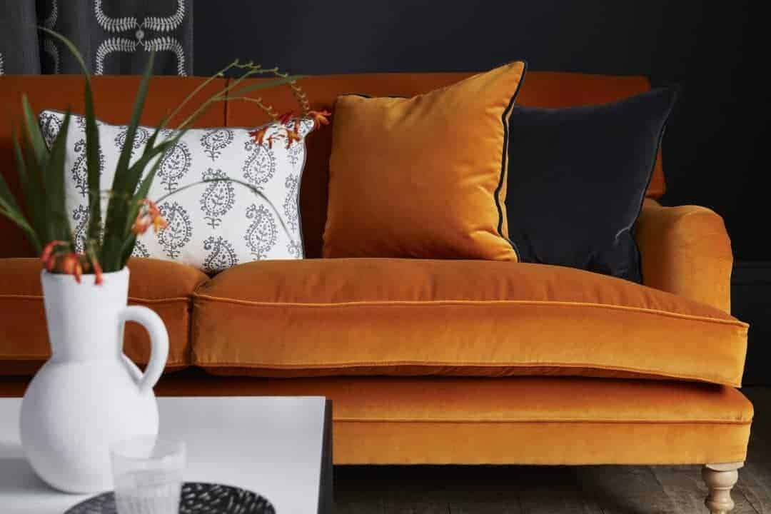 love this orange velvet sofa contrasted with printed grey and white linen and black velvet cushions. Click through for more velvet sofa velvet armchair and other velvet ideas you'll love
