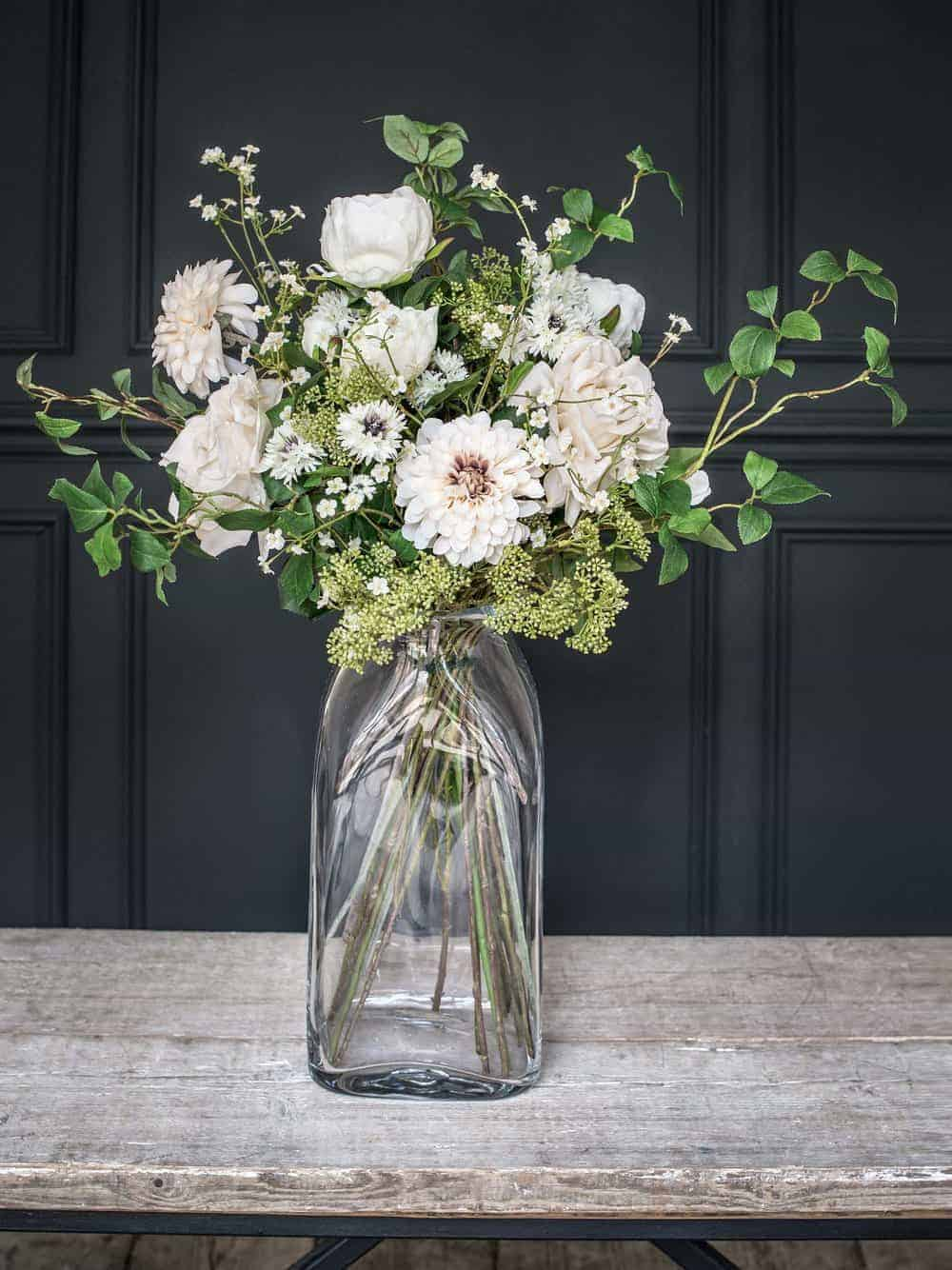 love these winter whites and blush pink dahlia faux flowers in large glass jar by philippa craddock. Perfect for creating long-lasting christmas flower arrangements. Click through for creative DIY christmas holiday flower ideas you'll love