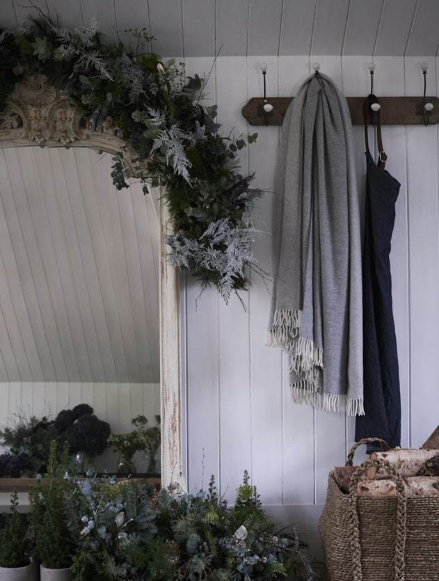 love this rustic farmhouse scandi christmas garland and hall decoration by Philippa Craddock using fir, eucalyptus, mini christmas trees, twigs, silver and white asparagus fern and foraged foliage. Click through for more DIY christmas flower decoration ideas you'll love to try this holiday season