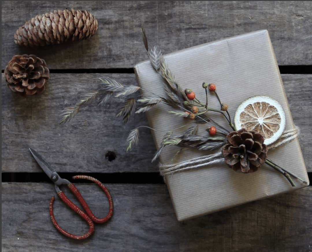 love this kraft paper gift wrap with sting, pine cones, berries and dried lime. Click through for more ethical eco-friendly and plastic free christmas gift wrapping ideas you'll love to try