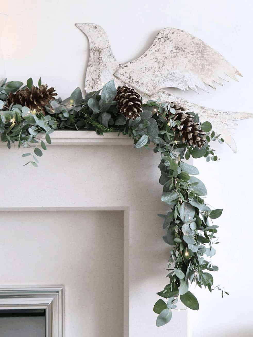 love this fresh christmas garland with eucalyptus pine cone and fairy lights on mantelpiece with vintage metal dove. Click through for more creative christmas flower arrangement DIY ideas to try in your own home this holiday period