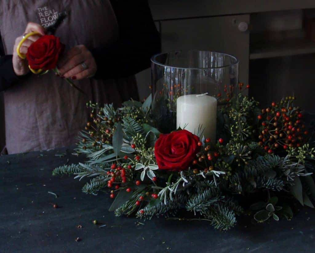 love this dark red rose, red berry and fir greenery candle christmas flower arrangement table centrepiece by The Real Flower Company. Click through for more creative and beautiful DIY christmas table centrepiece ideas you'll love to try this holiday season