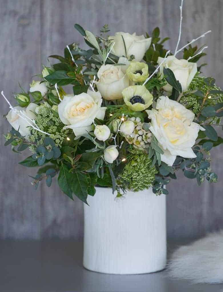 love this simple fresh white and lime green christmas flower arrangement with roses, anemone, eucalyptus, olive leaves and foraged greenery. Perfect in a simple, rustic white vase with white painted twigs and a string of lights. Click through for more christmas flower arrangement DIY ideas you'll love to try for adding natural festive beauty this holiday season