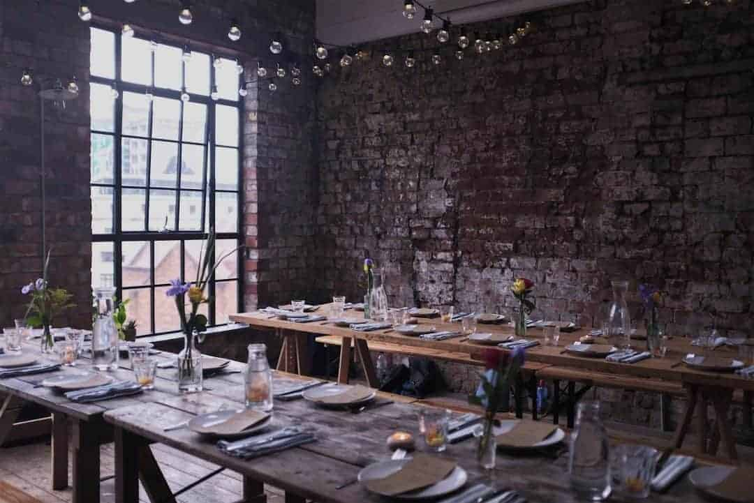 love this rustic warehouse with trestle tables decorated for the yoga brunch club table
