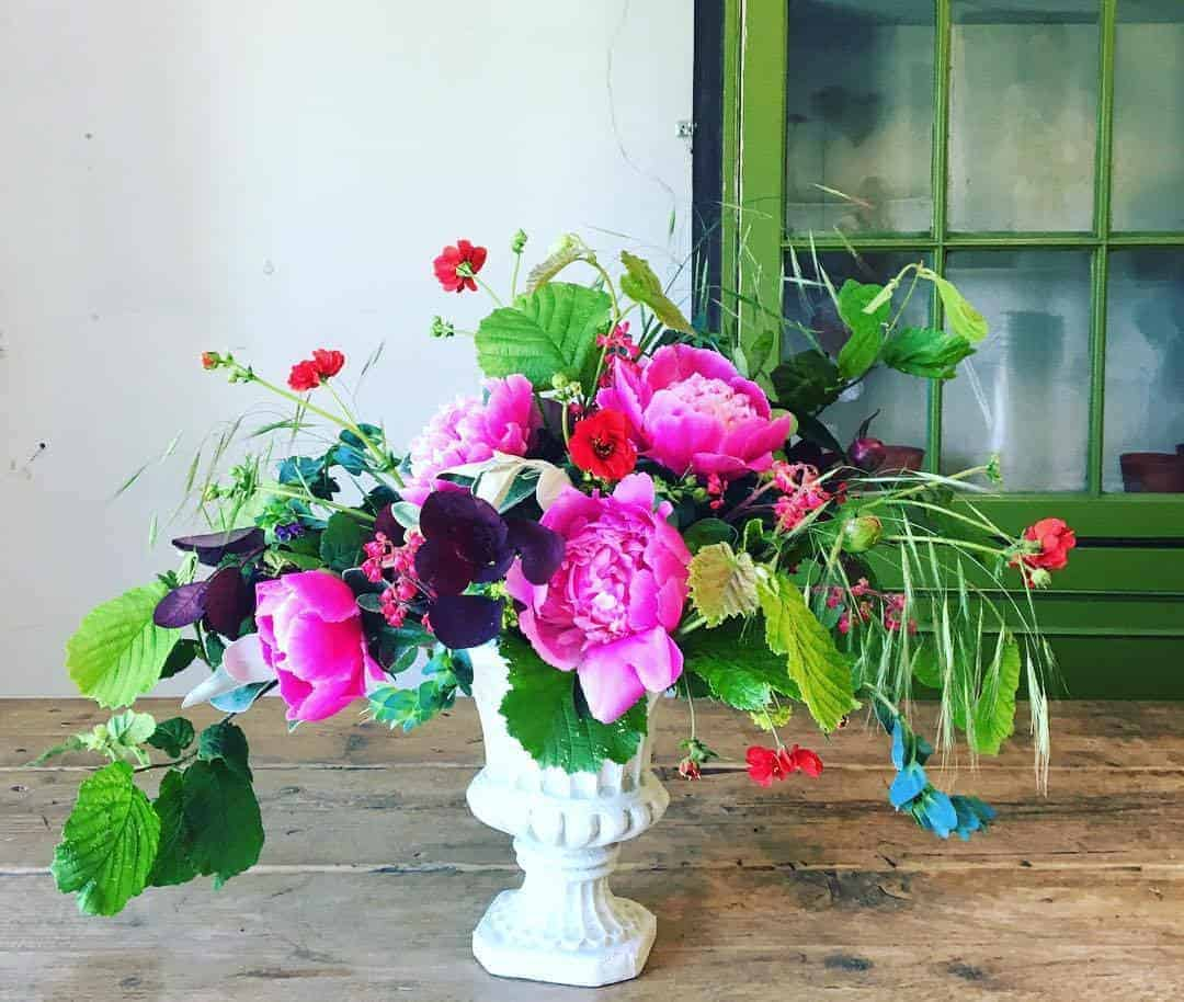 love this bright pink peonies with foraged foliage in white urn by Georgia of The Sussex Flower School. click through to find out more and to discover founder of the school, Georgia Miles' inspirations, simple pleasures and local loves