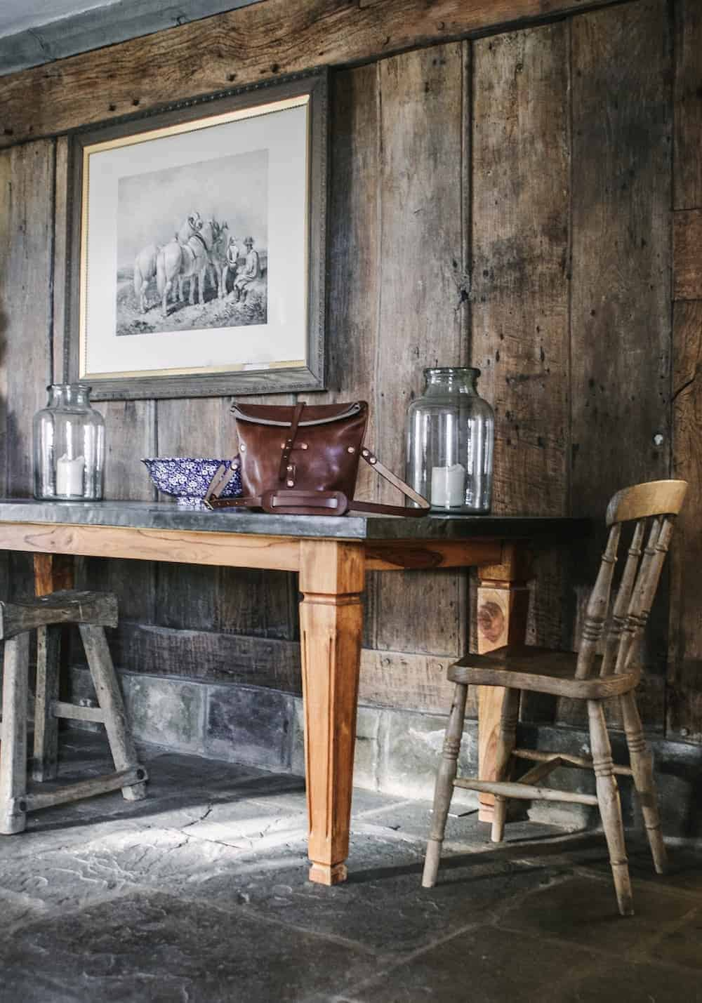 love this modern rustic wood panelled living room with galvanised top wooden table and old wooden farmhouse chairs at patrishow farm in wales - white washed walls, stone floor, reclaimed wooden units, galvanised metal worktop and butler sink with shelves of vintage and found country objects. This is the perfect dog friendly welsh holiday cottage. Click through to find out more and to see lots of beautiful images from our stay there
